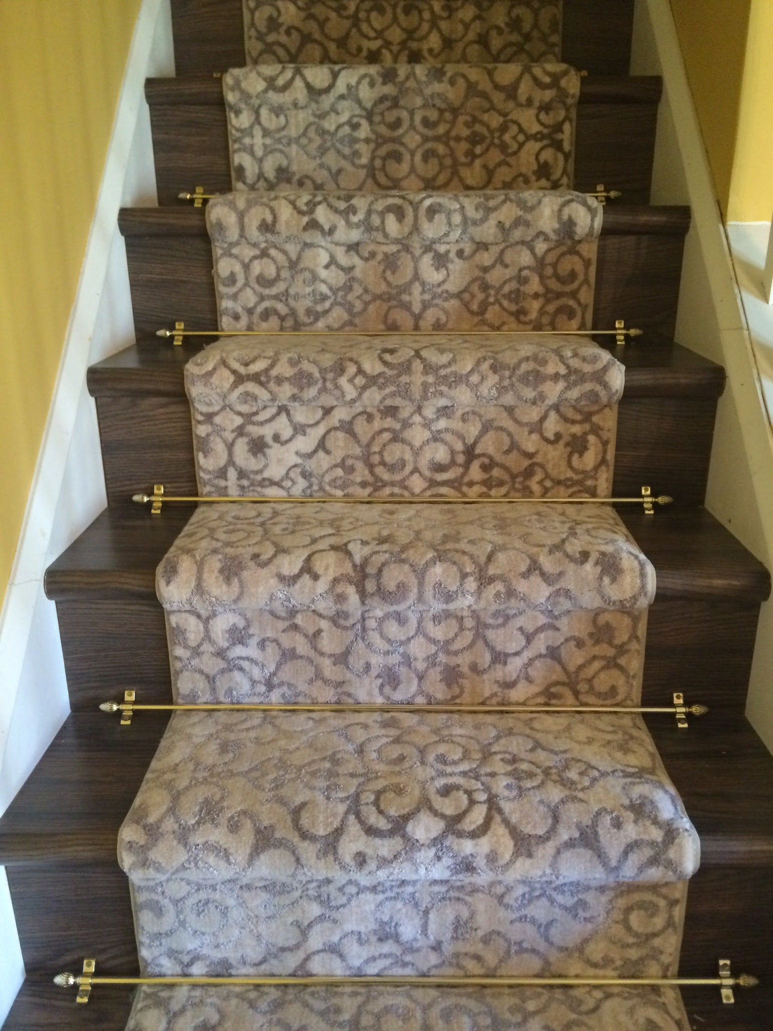 Bound wool blend woven carpet on steps with stair rods